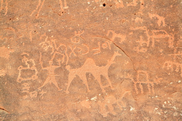 Images of people and camels carved into a rock wall, Wadi Rum