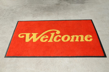 A Red Welcome Mat With Golden Letterings