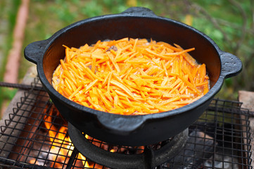 Carrots are roasted on surface of cauldron