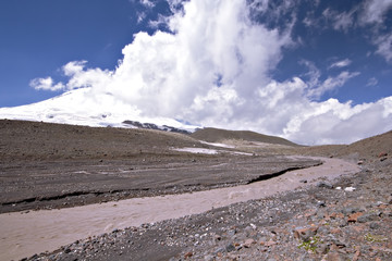 Glacier river against the peak Elbrus (5642m) in clouds
