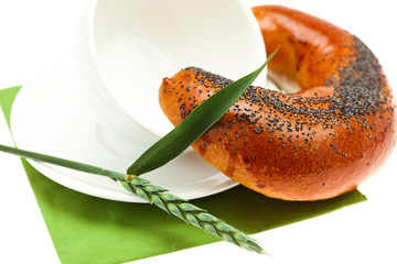 bread with poppy seeds, a cup and spike isolated on white