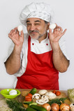 smiling chef in red apron cooking dinner poster