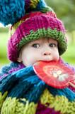 Mädchen mit Lolli und Mütze und Schal