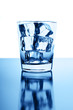 Glass with crystal clear ice cubes on glossy background
