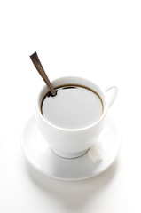 cup of coffee with teaspoon and sugar slices isolated on white