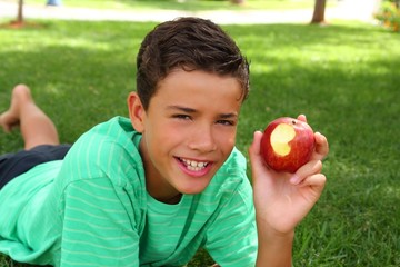 boy teenager eating red apple on garden grass