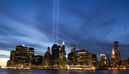 Light beams over Downtown Manhattan with a dramatic blue sky