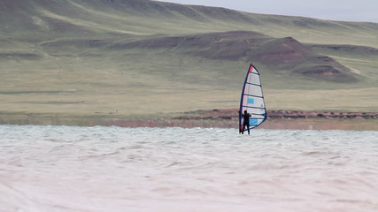 Windsurfer sailing fast in the big waves.