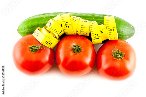 Measure with tomatoes and cucumber on a white background
