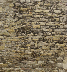 section of a very old yellow gray beige stone wall