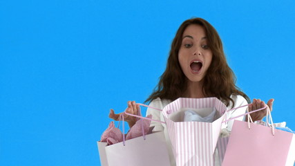 Suprised woman opening shopping bags standing on blue screen