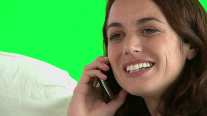 Close up of a female talking on phone against green screen
