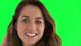 Beautiful hispanic woman smiling against a green screen