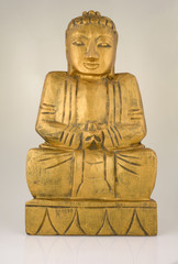 Carved wooden statue of Buddha in peacefull meditation.