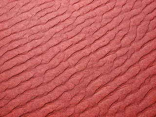 Abstract background of red sand ripples at the beach