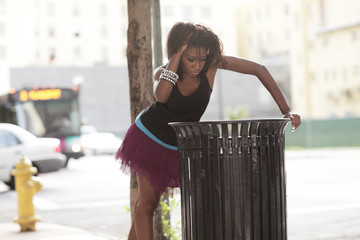 Woman looking for food in the trash bin
