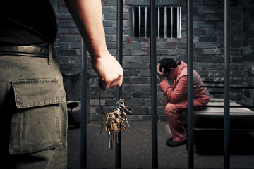 prison guard with keys outside dark prison cell
