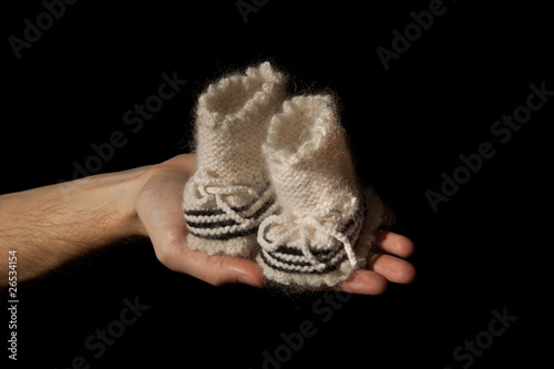papa's hand with baby's bootees