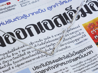 Close-up of Thai language newspaper and a pair of glasses.