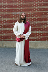 Man in Jesus robe and sash next to brick wall