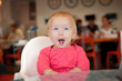 Adorable toddler girl sitting on chair in cafe near mother