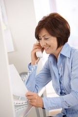 Smiling businesswoman on phone call reading paper.