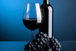 A glass of red wine with bottles and grapes on a blue background