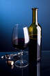 Glass of red wine with bottles on a blue background