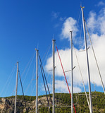 Sailboat Masts Against Blue Sky Background