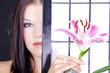 brünette beauty Frau blickt hinter Wand hervor mit rosa Lilie