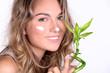 brünette beauty Frau blickt lächelnd mit Bambus und Creme