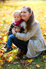 Mother and daughter outdoors at autumn day