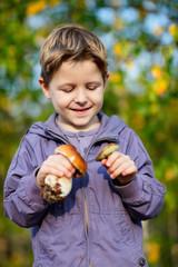 Happy boy with wild mushrooms