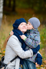 Boy kissing his mother outdoor