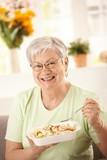 Fototapety Happy senior woman eating salad