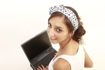 Junge Frau auf dem Boden lächelnd mit einem Laptop