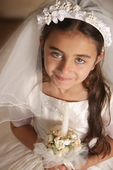 Girl in holy communion dress and veil, holding a candle