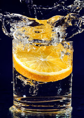 Slice of orange falling down in glass with water on deep blue