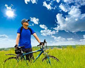 man with bike on green field