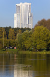 Park with pond and hight rise building at background poster