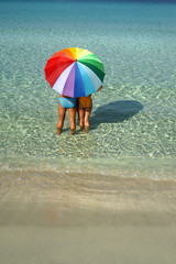 Paar mit Sonnenschirm am Strand