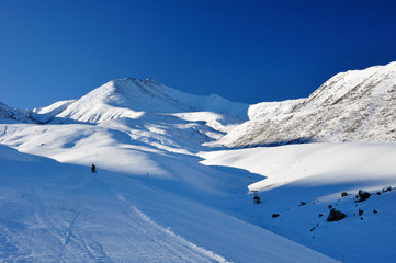 Winter in mountains with blue sky and skier