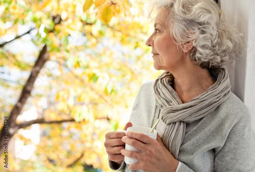 grauhaarige, attraktive Frau genießt den sonnigen Herbst - 26634736