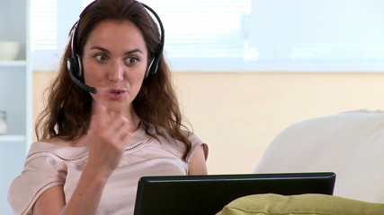 Joyful hispanic woman with earpiece and laptop lying at home