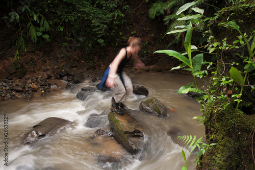 Woman crossing a river in Costa Rica
