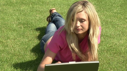 Beautiful woman using laptop lying in the garden