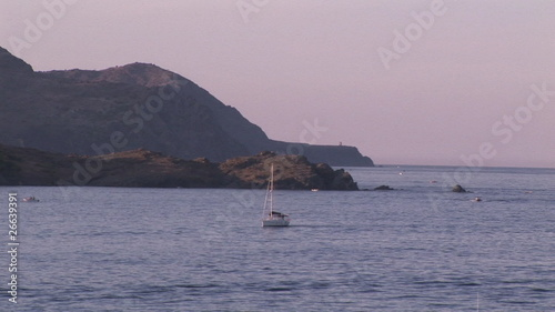 View of a sailboat arriving in the bay at sunset