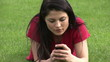 Captivating woman using cellphone lying on the grass