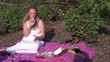 Single woman picnicking with bread and red wine in a vineyard