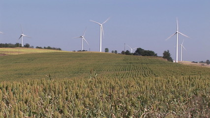 View of turning wind turbines standing in a field